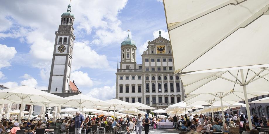 Friedenstafel auf dem Augsburger Rathausplatz: Mitgebrachtes Essen teilen - da fällt der Kontakt mit Fremden und Bekannten leicht.